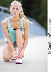 Young woman runner tying shoelaces on bridge