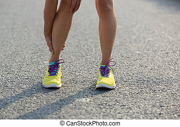 young woman runner with injured legs on city road