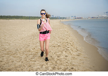 Young woman running across the beach