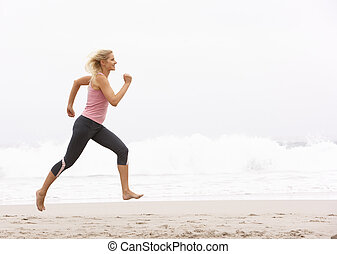 Young Woman Running Along Winter Beach