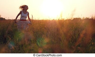 Young woman running and enjoying nature and sunlight in straw field