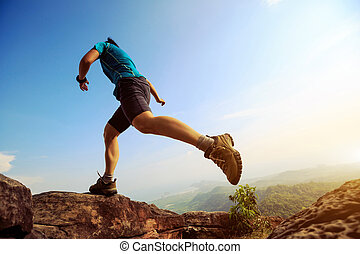 Young woman running and jumping on mountain peak