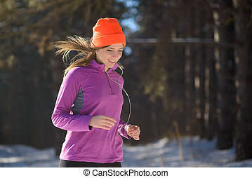 Young Woman Running in Beautiful Winter Forest at Sunny Frosty Day. Active Lifestyle Concept.