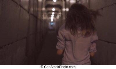 Dolly shot of young woman running in dark narrow corridor