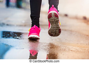 Young woman running in rainy weather
