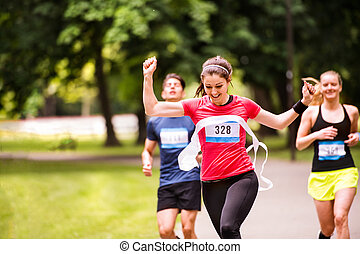 Young woman running in the crowd crossing the finish line.