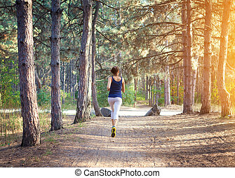 Young woman running on a rural road in forest