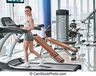 Young woman running on a treadmill in the gym