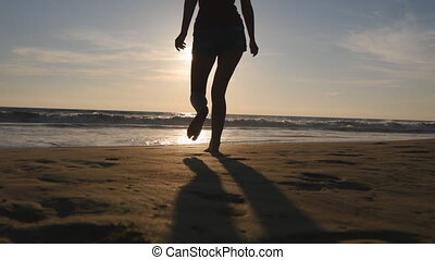 Young woman running on beach to the ocean at sunset and raised hands. Beautiful young girl going on sandy shore to the sea and enjoying freedom during vacation. Relax on summer holiday. Rear back view
