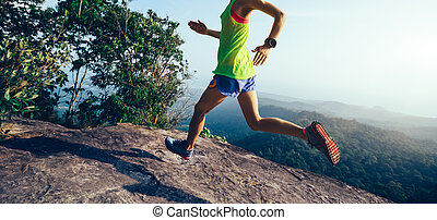 Young woman running on mountain peak cliff edge