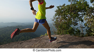 Young woman running on mountain peak