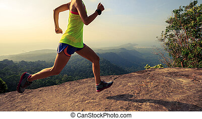 Young woman running on mountain top rock