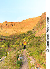 Young woman running on mountain trail
