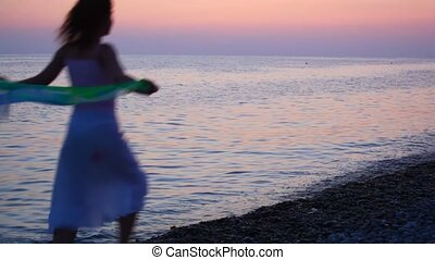 young woman running on pebble beach, sunset sea in background