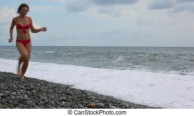 young woman running on pebble beach, surfing wave of sea in background