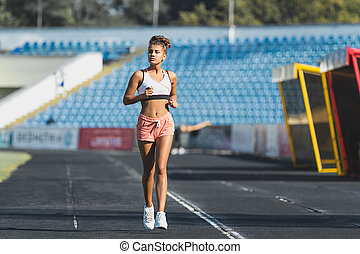 Young woman running on racetrack during training session