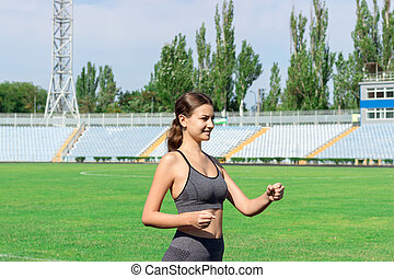 Young woman running on racetrack stadium. Training in the morning time. People sport and fitness concept