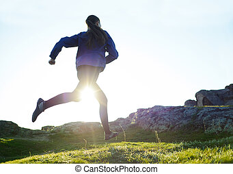 Young Woman Running on Rocky Mountain Trail at Sunset. Active Lifestyle Concept