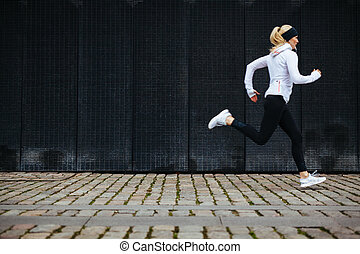 Young woman running on sidewalk in morning - View of young...