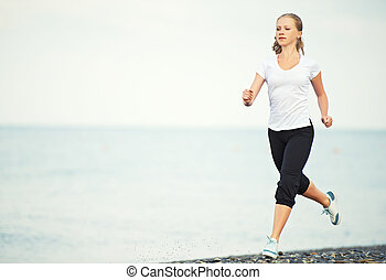 young woman running on the beach on the coast of the Sea