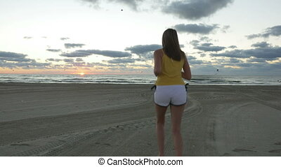 Young woman running on the beach towards sea at sunrise