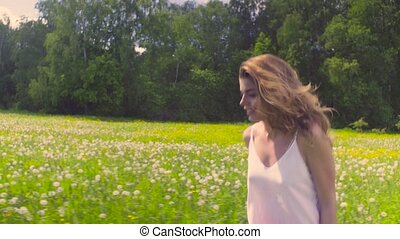 Young woman running on the meadow - Rear view of young woman...