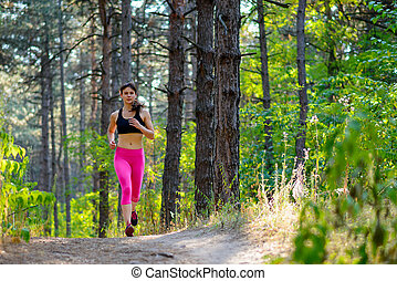Young Woman Running on the Trail in the Beautiful Wild Forest. Active Lifestyle Concept. Space for Text.