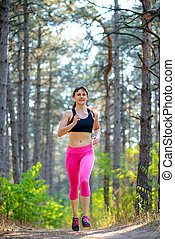 Young Woman Running on the Trail in the Beautiful Wild Pine Forest. Active Lifestyle Concept. Space for Text.