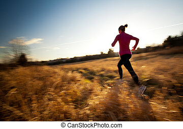 Young woman running outdoors on a lovely sunny winter/fall ...