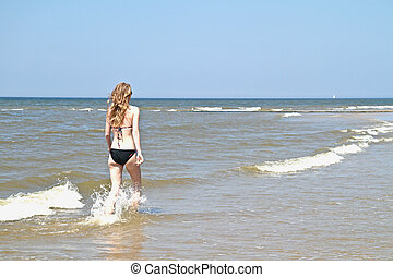 Young woman running through the water from the ocean