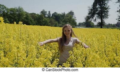 Young Woman Running through Yellow Field Touching Flowers HD