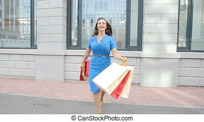 young woman running with shopping bags in hands outdoors