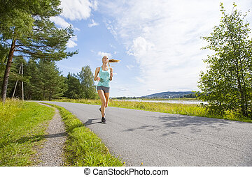 Young woman runs fast on a road in the forest
