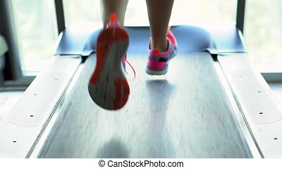 young woman runs on a treadmill in the gym, slow motion, back view