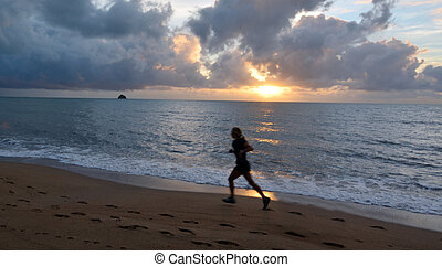 Young woman runs on the beach