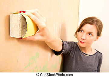 young woman sanding wall