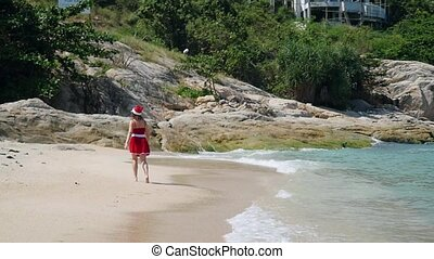 Young woman Santa Claus walking on the beach near the sea in slow motion. Christmas and new year vacation on Koh Samui, Thailand. 1920x1080