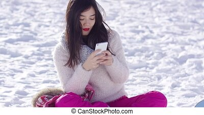 Young woman sat on snow texting on mobile
