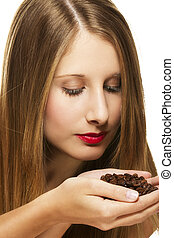 young woman scenting on a handful of coffee beans on white background