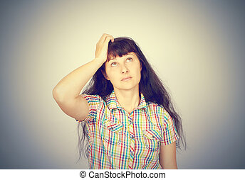 young woman scratching head, thinking daydreaming deeply about something