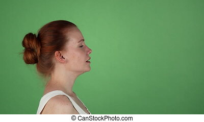 Young woman screaming on green chromakey background -...