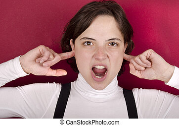 young woman screams with fingers in her ears