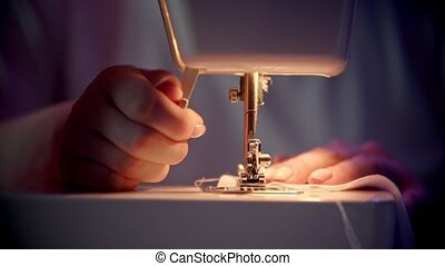Young woman seamstress preparing the machine for sewing. Mid shot