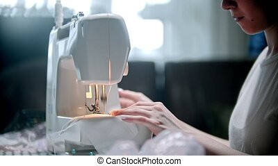 Young woman seamstress sewing a white mask. Mid shot