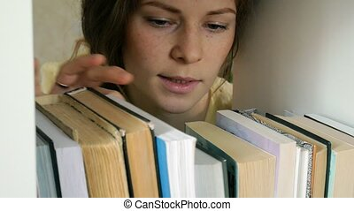 young woman searching for a book. student selecting bookshelf library. female taking book from shelf in library.