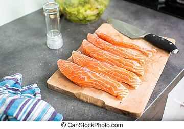 Young woman seasoning a salmon filet in her modern kitchen