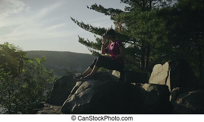 Young woman seats on the mountain rocks and drinks water