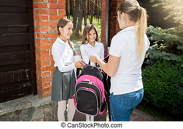Young woman seeing off her daughters to school - Beautiful ...