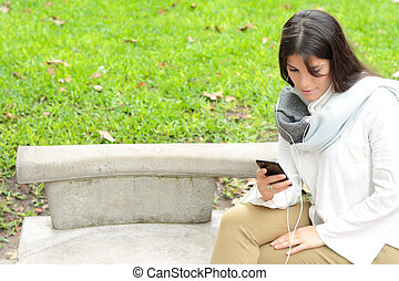 Young woman sending message with smartphone.