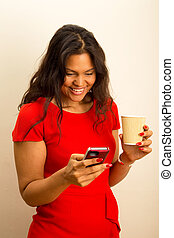 young woman sending text with coffee